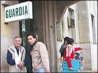 Pacientes esperan en la puerta de entrada de la guardia de un hospital, mientras otros salen.