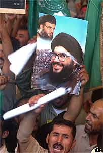 Pilgrims hold pictures of Nasrallah in Najaf, Iraq