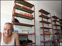 A Lebanese man sits in a shop nearly depleted of food supplies in Tyre