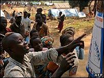 Habitantes leen información electoral en Congo.
