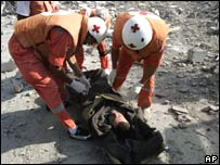 Red Cross paramedics evacuate an injured Lebanese man in Qana after an Israeli airstrike