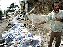 A Lebanese man from the southern village of Qana burst into tears as he shows covered bodies removed from under the rubble of the demolished building.