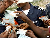 Congolese voters show their voting cards to a police officer at a polling station in Kinshasa, DR Congo