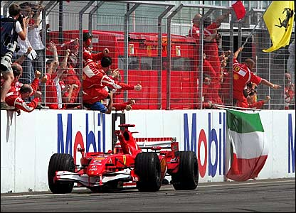 Michael Schumacher takes the congratulations of his Ferrari mechanics after winning the German Grand Prix
