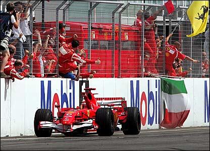 Michael Schumacher takes the congratulations of his Ferrari mechanics after winning the German Grand Prix