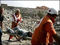 Paramedics carry an injured Lebanese from the rubble
