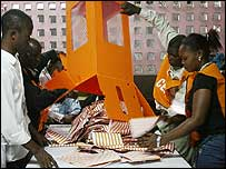 Election workers empty a ballot box