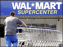 Man with shopping trolleys outside a Wal-Mart store