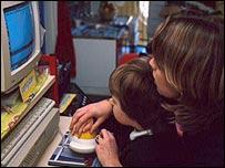 Niño y madre trabajan en computadora.