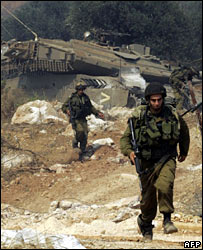 Israeli troops secure an area as armoured vehicles return from Lebanon