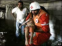 Emergency worker carrying body of a child