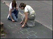 The children drawing chalk markings on the pavement