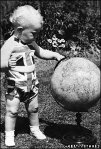 A toddler plays with a globe.