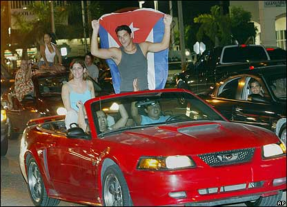 Couple ride in a convertible in the streets of Hialeah, Florida