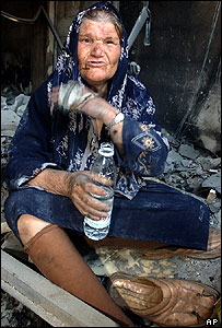 An elderly Lebanese drinks water as she waits to be helped after coming out from shelter during a lull in the fighting in the village of Bint Jbeil, southern Lebanon
