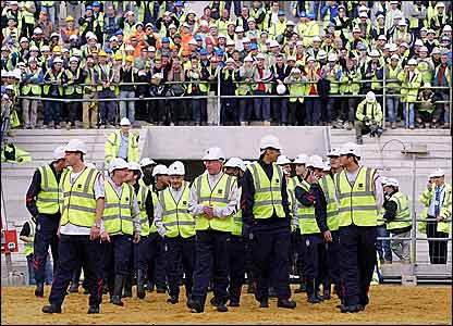 The England football team, clad in hard hats and yellow vests, visit the partially-built stadium