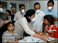 Indonesian Health Minister Siti Fadilah Supari talks to one of the children affected at the hospital in Medan