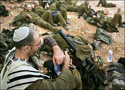 Israeli reservist prays while other soldiers rest after returning from Lebanon