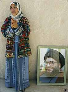 Woman mourns in prayer at Al Jamaliyeh next to picture of Hezbollah leader Sheikh Hassan Nasrallah