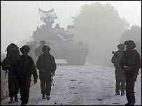 Israeli soldiers with tank in background