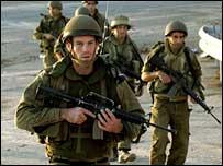 Israeli reserve soldiers advance at the Israeli-Lebanese border