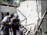Two Israeli police officers console each other as they stand by a house damaged by a Hezbollah rocket
