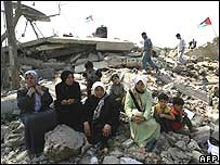 Palestinian women sit in the ruins of a building destroyed by an Israeli jet in the north Gaza Strip
