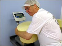 John Spence at work weighing one of his cheddar rounds