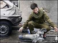 Israeli soldier examines a Katyusha-style rocket fired by Hezbollah into northern Israel on 30 July