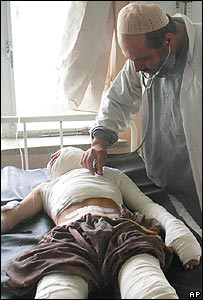 A doctor checks on a man wounded in the car bomb attack in Panjwayi district, Kandahar, on 3 August