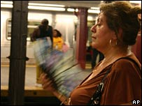 A woman fans herself in the heat on the New York subway