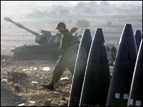 An Israeli soldier walks outside a mobile artillery unit at a military staging area along the Israel-Lebanon border