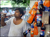 An Indian man drinking a cola