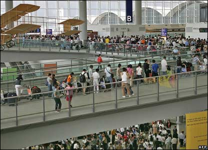 Passengers wait in line at the airport in Hong Kong