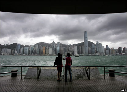 Hong Kong residents watch the gathering clouds
