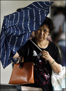 A Hong Kong resident uses an umbrella to shelter from the weather