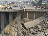 People inspect the destroyed bridge at Halat which linked Beirut to north Lebanon