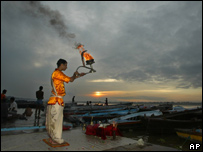 A Hindu priest conducts morning prayers on the banks of the Ganges