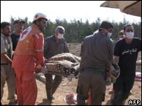 Red Cross and civil defence officials carry away the body of a farm worker in the village of Qaa
