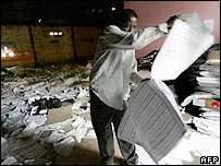 An unidentified man looks at ballot papers at an open liaison office of the Electoral Commission in Kinshasa