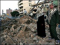 Lebanese women inspect a road in the city of Tyre, after it was hit by an Israeli missile strike