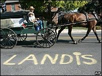 Vagón tirado por caballos junto a aviso de Landis.