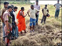 Villagers look at dried up paddy fields