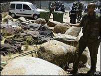 An Israeli soldier stands next to the covered bodies of Israelis killed in a Hezbollah rocket attack on Kfar Giladi
