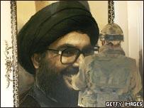 جندي اسرائيلي أمام صورة لنصر الله في منزل في يارون