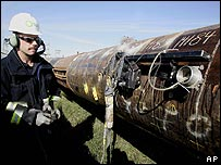 BP engineer examining section of oil transit pipeline