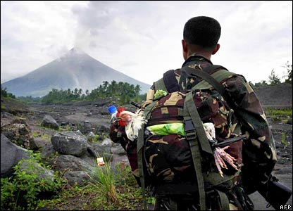 A Philippine soldier carrying a chicken in his backpack looks up at the volcano