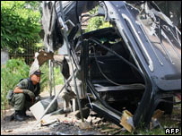 Soldier looks at a bomb-out car, May 2006