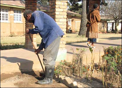 Man sweeping up hospital grounds
