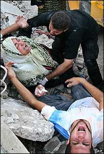 Khadijeh Saleh y su hijo reaccionan después de que sus familiares quedaran atrapados en un edificio derrumbado por la aviación israelí, en el pueblo libanés de Ghassaniyeh.